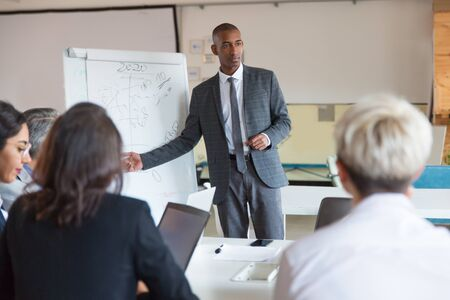Workers discussing ideas during presentation of new project. Serious speaker near whiteboard. Business meeting concept Stock Photo