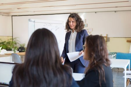 Businesswoman giving presentation to female colleagues. Group of professional businesswomen discussing new project at workplace. Women in business concept Stok Fotoğraf