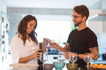 Smiling woman holding bottle of red wine and taking corkscrew. Happy young man and woman opening wine at kitchen. Wine tasting concept