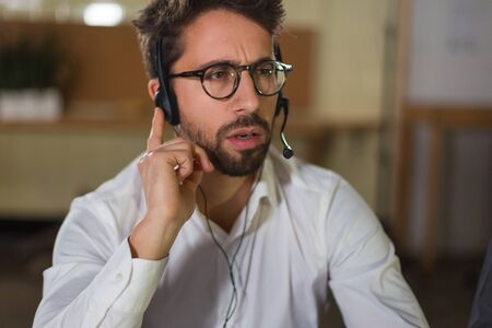 Thoughtful young man receiving incoming call. Front view of call center operator at work. Call center concept