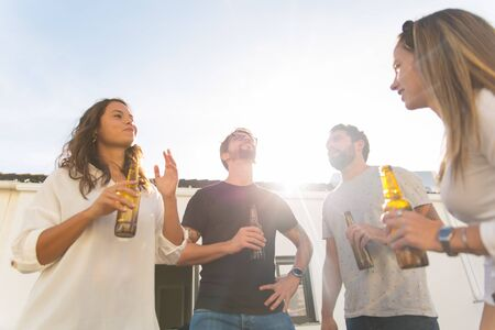 Cheerful young people hanging out with beer. Low angle shot of cheerful friends holding beer bottles. Leisure, friendship concept