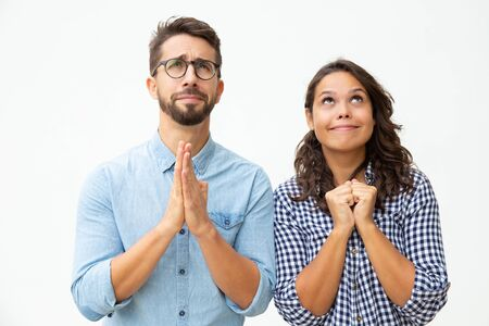 Emotional young couple praying together. Front view of hopeful young man and woman praying and looking up on white background. Hope concept