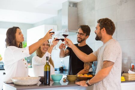Cheerful friends clinking glasses with red wine. Friends tasting wine at kitchen. Wine tasting concept