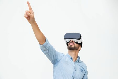 Young man using VR headset. Handsome young man using virtual reality headset and pointing up with finger on white background. Wearable technology concept