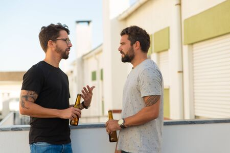 Two focused young men talking while drinking beer. Thoughtful friends communicating on balcony. Leisure, friendship concept