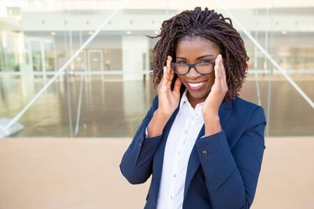 Attractive content businesswoman adjusting eyeglasses. Portrait of beautiful young African American businesswoman wearing spectacles and smiling at camera. Profession concept