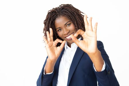Businesswoman showing ok sign and smiling at camera. Portrait of cheerful young African American businesswoman showing ok sign and looking at camera. Approving concept