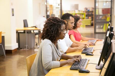 Estudiantes concentrados usando computadoras en la biblioteca. Jóvenes reflexivos que buscan información con ayuda de computadoras. Educación, concepto de tecnología