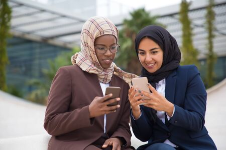 Front view of smiling managers using smartphones. Cheerful Muslim businesswomen resting on street with digital devices. Technology concept