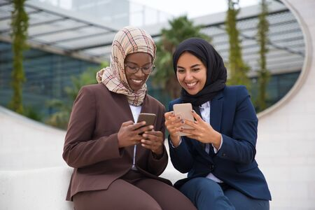 Smiling managers sitting on street and using smartphones. Cheerful Muslim businesswomen resting on street with digital devices. Technology concept