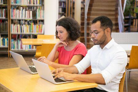 Dwóch skoncentrowanych studentów korzystających z laptopów siedzących w bibliotece. Skoncentrowani ludzie uczący się razem z laptopami. Technologia, koncepcja edukacji Zdjęcie Seryjne