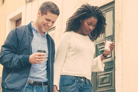 Cheerful young mix raced couple walking outdoors and minding their steps. Happy Caucasian man and black woman with takeaway coffee holding hands and looking down. Watching steps concept