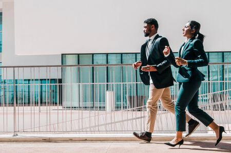 Business man and woman running outdoors. Business people wearing formal clothes with building in background. Business competition concept. Side view. Standard-Bild