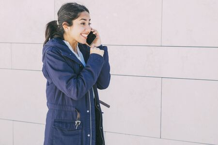 Cheerful happy student girl getting good news from phone talk. Surprised overjoyed young woman speaking on cellphone. Communication or good news concept