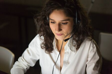 Concentrated call center operator in dark office. Focused young businesswoman in headset working in dark office late at night. Client support concept