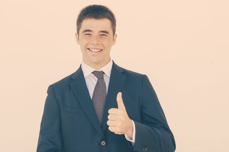 Cheerful sales agent recommending product or service. Young man in office jacket and tie showing thumb up and smiling at camera. Like gesture concept