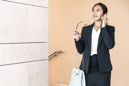 Cheerful business lady talking on phone in office hall. Smiling young woman in formal suit holding glasses, looking at copy space on wall and sharing good news on cellphone. Good news concept Stock fotó