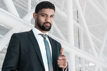 Serious black business man showing thumb up. Guy standing with building constructions in background. Promotion concept. Front view. Standard-Bild