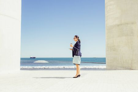 Businesswoman spending her coffee break on seafront. Young woman in formal suit and sunglasses standing by sea, holding handbag, smartphone and takeaway cup. Business woman by sea concept