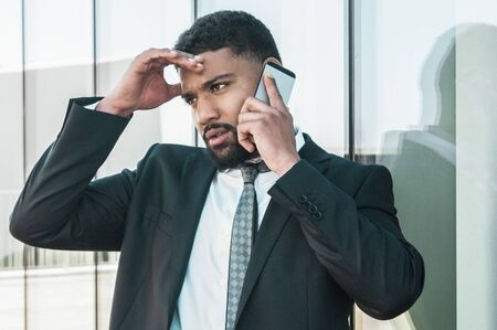 Concerned businessman speaking on phone outdoors and getting bad news. Young Latin man in suit and tie touching head with upset face and talking on cell outside. Business troubles concept Stock Photo