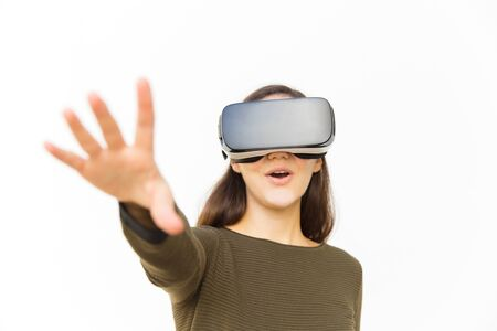 Excited young woman testing VR headset. Smiling lady with outstretched arm experiencing virtual reality glasses. Technology concept