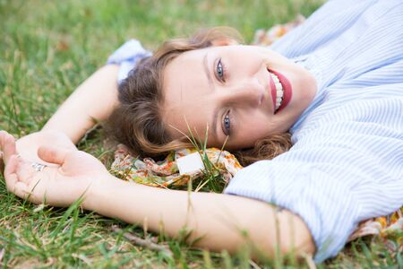 Smiling woman lying on ground in park and looking at camera. Beautiful lady relaxing outdoors. Leisure, relaxation concept