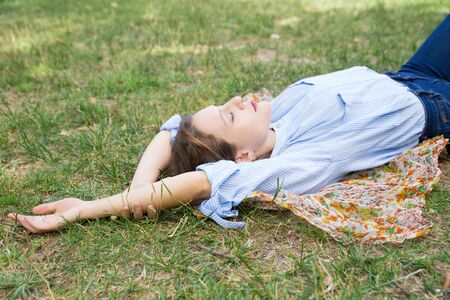Relaxed young woman lying on headkerchief on ground in park. Beautiful lady relaxing outdoors. Leisure, relaxation concept
