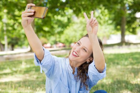 Smiling young woman showing peace sign while taking selfie. Cheerful lady holding phone in outstretched arm and gesturing. Technology, self portrait concept Imagens