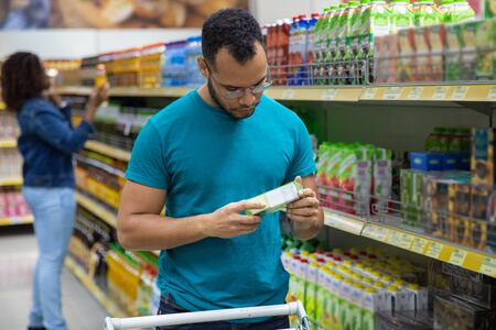 Focused African American man reading information on packaging. Concentrated bearded guy buying food at supermarket. Shopping concept