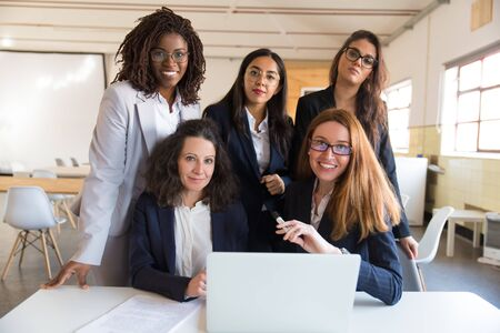 Group of smiling businesswomen looking at camera. Front view of professional office managers posing near table with laptop. Business, teamwork concept