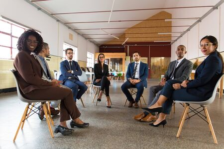 Business people sitting in chairs in circle. Confident employees looking at camera. Teambuilding, training concept Stock Photo