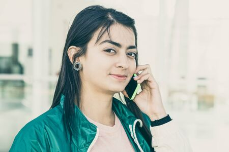 Front view of pretty young mixed-race woman in green jacket talking on phone, looking at camera. Lifestyle concept