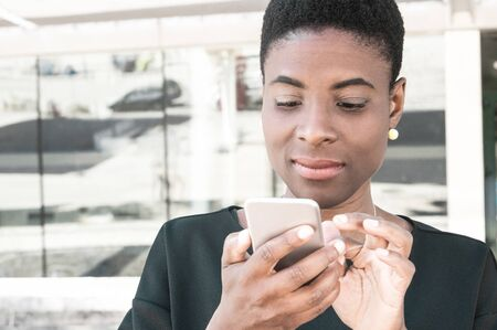 Focused African American woman using online mobile app. Satisfied black lady holding using smartphone outside, looking at screen with light smile. Digital technology concept