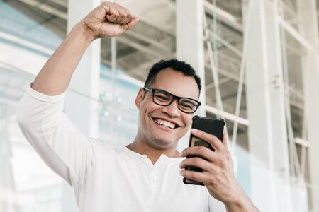 Bottom view of smiling young mixed-race man in spectacles and white T-shirt finishing phone call, receiving good news, exulting. Lifestyle, work concept Banco de Imagens