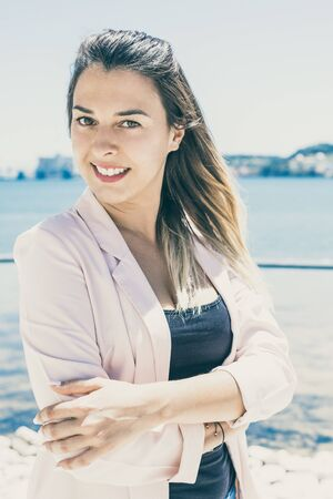 Positive office employee relaxing by river during work break. Happy cheerful young woman in white jacket standing for camera with arms folded l and smiling. Walk by river concept Stock fotó