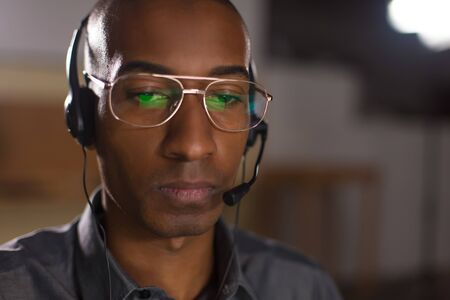 Focused African American man with headset looking down. Front view of call center operator. Call center concept