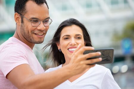 Happy multiracial friends taking self portrait with smartphone. Cheerful couple posing for selfie on street. Concept of self portrait Imagens