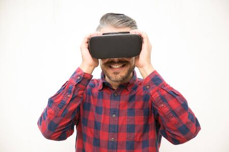 Excited young guy holding VR headset. Studio shot of young man testing virtual reality glasses. Technology concept
