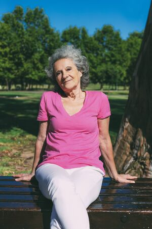 Peaceful old lady posing in park. Senior grey haired woman in casual sitting on bench, leaning on hands and looking at camera. Old woman in park concept