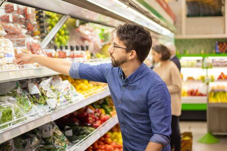 Young man shopping in grocery store. Side view of focused man and woman holding shopping baskets and choosing fresh fruits and vegetables in supermarket. Shopping concept Banque d'images
