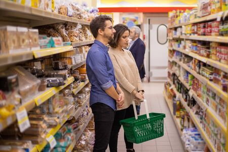 Couple looking at shelves in grocery store. Focused young man and woman holding basket and choosing products in supermarket. Shopping concept Foto de archivo