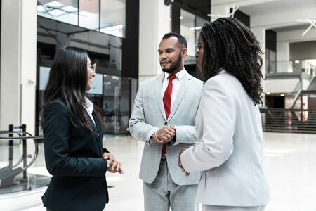 Agent and clients meeting and discussing deal in office hall. Business man and women standing in hallway and talking. Negotiation or dealing concept