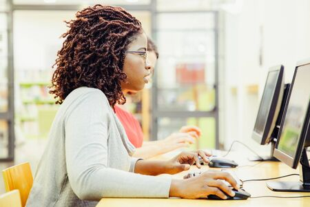 Focused female student excited with online test in computer class. Black woman in casual sitting at table, using desktop, typing, looking at monitor with open mouth. Excites student concept Banco de Imagens