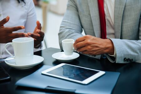 Business partners discussing work issues over cup of coffee. Hands of business people sitting at table with tablet in cafe, drinking coffee, gesturing. Coffee break concept