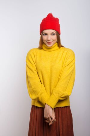 Shy smiling woman in stylish knitwear. Beautiful happy young woman in red knitted hat and yellow sweater smiling and looking aside isolated on white background. Style and emotion concept