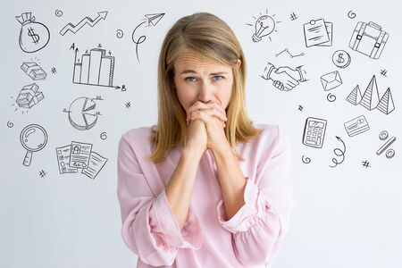 Woman worried about project with hand drawn business sketches. Frowning emotional employee waiting for performance appraisal results and holding hands near mouth. Fear concept