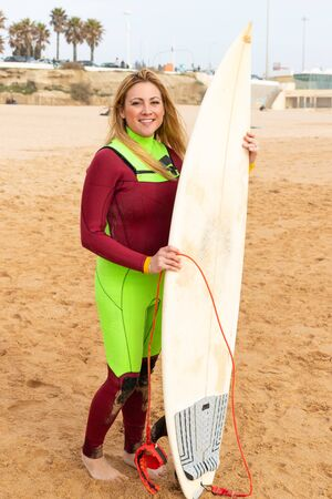 Happy female surfer smiling at camera. Cheerful middle aged woman in wetsuit holding surfboard and looking at camera on sea coast. Water sport concept