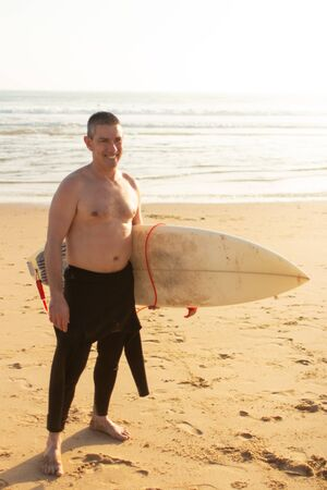 Cheerful man with surfboard on beach. Happy middle aged man in wetsuit holding surfboard and standing on sandy sea coast. Surfing concept