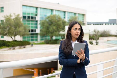 Serious young woman with tablet pc. Focused young businesswoman holding digital tablet and looking aside in urban city. Wireless technology concept