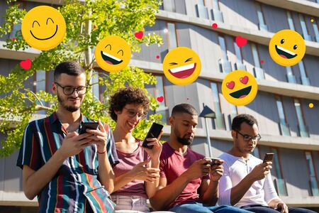 Group of different young people using smartphones outdoors. Men and woman sitting near city building, texting message with online chat icons above. Digital communication concept Archivio Fotografico
